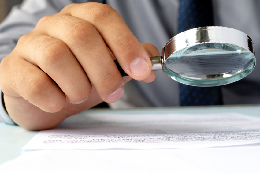 magnifying glass in hand, a businessman