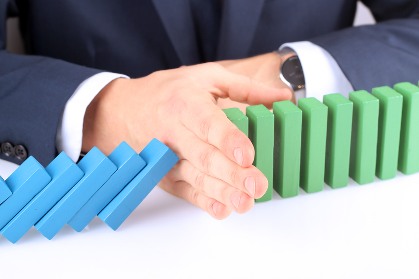 Close-up of businessman stopping the effect of domino with hand