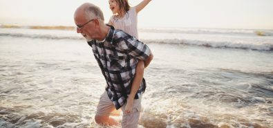 Fun, Energetic Grandpa Playing In Waves With Young Grandchild – Girl – On Beach At Sunset – Shoulder Ride