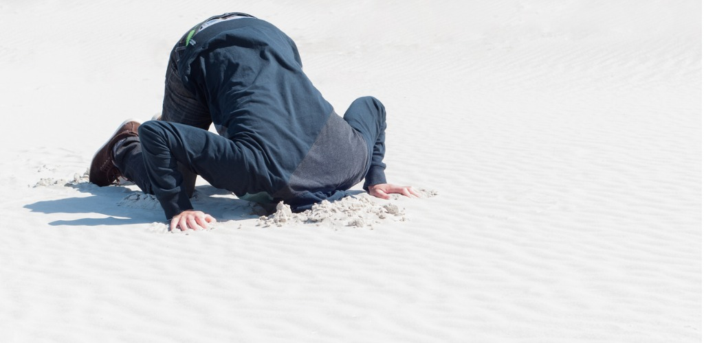 young-male-hiding-head-in-sand-picture-id519012383