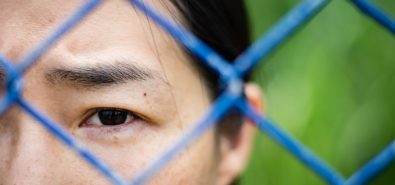 woman face behind a fence